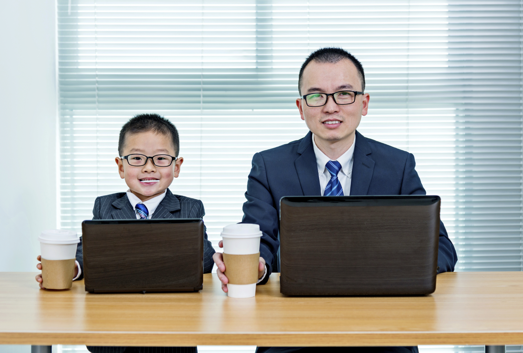 Father and son using laptops in office room.