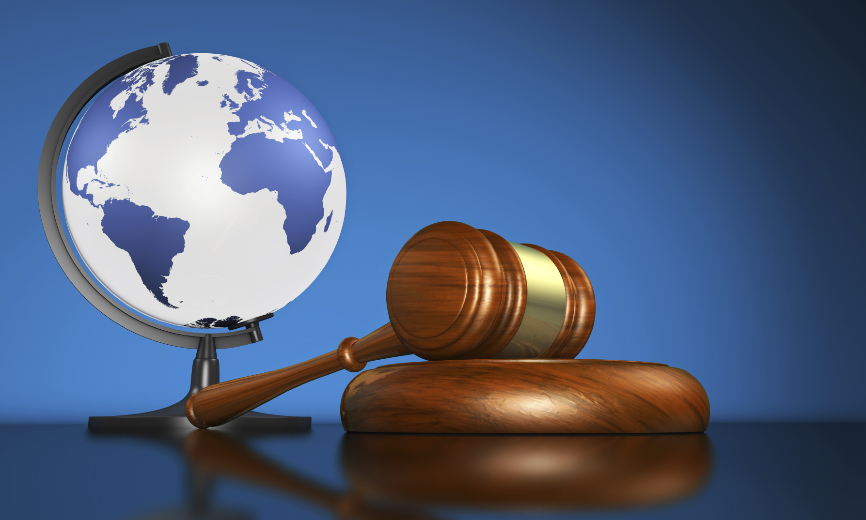 International law systems, justice, human rights and global business education concept with world map on a school globe and a gavel on a desk on blue background.